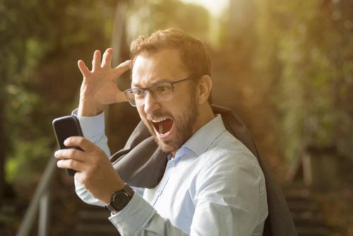 angry young man yelling at phone