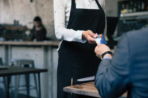 man handing waitress a credit card at a restaurant